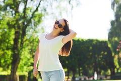 Mujer joven sonriente con las gafas de sol en parque Fotos de archivo