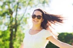 Mujer joven sonriente con las gafas de sol en parque Imagen de archivo libre de regalías