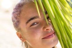 mujer joven sonriente con las hojas de la palmera Imágenes de archivo libres de regalías