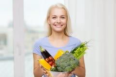Mujer joven sonriente con las verduras en casa Fotografía de archivo libre de regalías