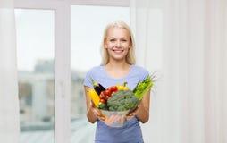 Mujer joven sonriente con las verduras en casa Imágenes de archivo libres de regalías