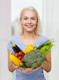 Mujer joven sonriente con las verduras en casa Fotos de archivo libres de regalías