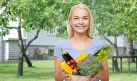 Mujer joven sonriente con las verduras en jardín Fotos de archivo libres de regalías