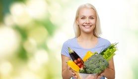 Mujer joven sonriente con las verduras sobre verde Foto de archivo libre de regalías