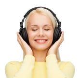 Mujer joven sonriente con los auriculares Fotos de archivo libres de regalías