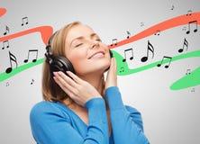 Mujer joven sonriente con los auriculares Imágenes de archivo libres de regalías