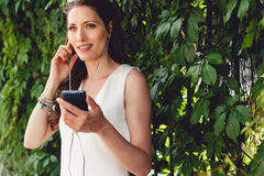 Mujer joven sonriente con los auriculares en fondo del follaje Imagen de archivo libre de regalías