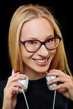 Mujer joven sonriente con los auriculares y los vidrios Foto de archivo libre de regalías