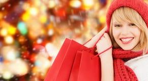 Mujer joven sonriente con los bolsos de compras Fotografía de archivo libre de regalías