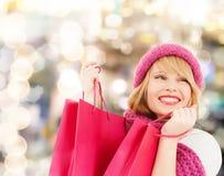 Mujer joven sonriente con los bolsos de compras Fotos de archivo
