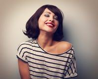 Mujer joven sonriente con los ojos cerrados que ríe con el pelo corto Foto de archivo libre de regalías