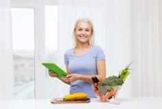 Mujer joven sonriente con PC de la tableta que cocina en casa Imagen de archivo