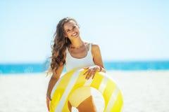 Mujer joven sonriente con salvavidas inflable amarillo en la playa fotos de archivo libres de regalías