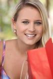 Mujer joven sonriente con un bolso del almacén Imagen de archivo