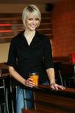 Mujer joven sonriente con un vidrio de zumo de naranja fotografía de archivo libre de regalías