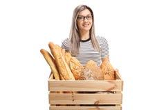 Mujer joven sonriente con una caja por completo de panes del pan fotos de archivo libres de regalías