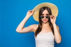 Mujer joven sonriente de la belleza con las gafas de sol y el sombrero en un estilo moderno en un fondo de una pared azul Imagenes de archivo
