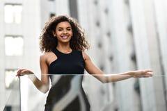 Mujer joven sonriente de la raza mixta en la calle fotos de archivo libres de regalías