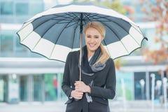 Mujer joven sonriente debajo de un paraguas abierto Fotografía de archivo