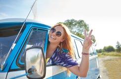 Mujer joven sonriente del hippie que conduce el coche del minivan Imágenes de archivo libres de regalías