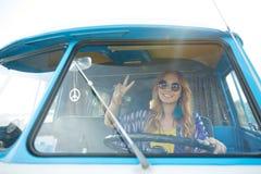 Mujer joven sonriente del hippie que conduce el coche del minivan Imagen de archivo