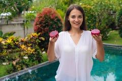 Mujer joven sonriente del retrato que sostiene dos frutas del dragón, pitaya en sus manos cerca de la piscina imagenes de archivo