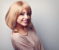Mujer joven sonriente dentuda feliz con el pelo rubio corto Cl entonado Imagen de archivo
