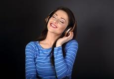 Mujer joven sonriente dentuda hermosa en ropa azul que escucha Fotografía de archivo