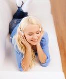 Mujer joven sonriente en auriculares en casa Fotos de archivo libres de regalías