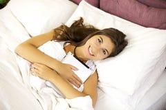Mujer joven sonriente en cama con la tablilla Imagenes de archivo