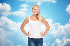 Mujer joven sonriente en camisa blanca en blanco y vaqueros Fotografía de archivo