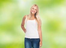 Mujer joven sonriente en camisa blanca en blanco y vaqueros Imágenes de archivo libres de regalías