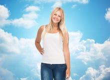 Mujer joven sonriente en camisa blanca en blanco y vaqueros Foto de archivo libre de regalías