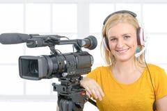 Mujer joven sonriente en camiseta amarilla con el camcorde profesional Imagenes de archivo
