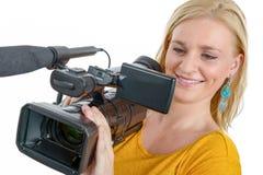 Mujer joven sonriente en camiseta amarilla con el camcorde profesional Foto de archivo libre de regalías