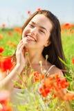 Mujer joven sonriente en campo de la amapola Fotografía de archivo