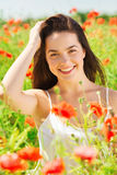 Mujer joven sonriente en campo de la amapola Foto de archivo libre de regalías
