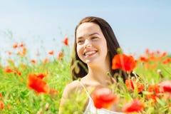 Mujer joven sonriente en campo de la amapola Fotos de archivo libres de regalías