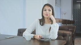Mujer joven sonriente en el café con los auriculares que escucha la música en una tableta Fotografía de archivo libre de regalías