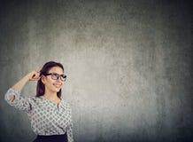 Mujer joven sonriente en el pensamiento de los vidrios Fotografía de archivo libre de regalías