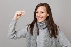 Mujer joven sonriente en el suéter gris, tableta de la medicación de la tenencia de la bufanda, píldora de aspirin aislada en fon imagenes de archivo