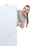 Mujer joven sonriente en el suéter que mira hacia fuera de la cartelera en blanco Imágenes de archivo libres de regalías