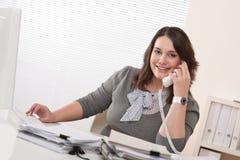 Mujer joven sonriente en el teléfono en la oficina Foto de archivo