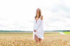 Mujer joven sonriente en el vestido blanco en campo de cereal Fotografía de archivo