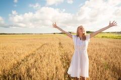 Mujer joven sonriente en el vestido blanco en campo de cereal Imagen de archivo libre de regalías