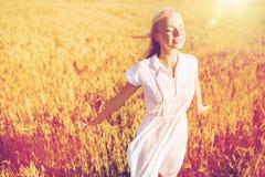 Mujer joven sonriente en el vestido blanco en campo de cereal Imágenes de archivo libres de regalías