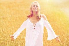 Mujer joven sonriente en el vestido blanco en campo de cereal Foto de archivo