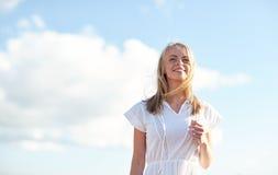 Mujer joven sonriente en el vestido blanco sobre el cielo azul Imagen de archivo