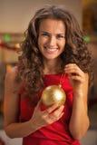 Mujer joven sonriente en el vestido rojo que sostiene la bola de la Navidad Imagen de archivo