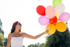 Mujer joven sonriente en gafas de sol con los globos Imagen de archivo libre de regalías